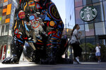 A woman leans against a sculpture outside a Starbucks store in Beijing on Tuesday, May 21, 2019. As the US and China trade war escalates, Chinese officials may target operations of American companies in China by slowing customs clearance for their goods and stepping up regulatory scrutiny that can hamper operations. (AP Photo/Ng Han Guan)