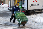 A worker wheels a food delivery trolley in the snow and ice in Madrid, Spain, Tuesday, Jan. 12, 2021. Schools remain closed in Madrid and many other parts of central Spain, with authorities focusing on reopening roads and stocking up supermarkets, struggling with the largest snowfall in half a century and record-low temperatures. (AP Photo/Paul White)