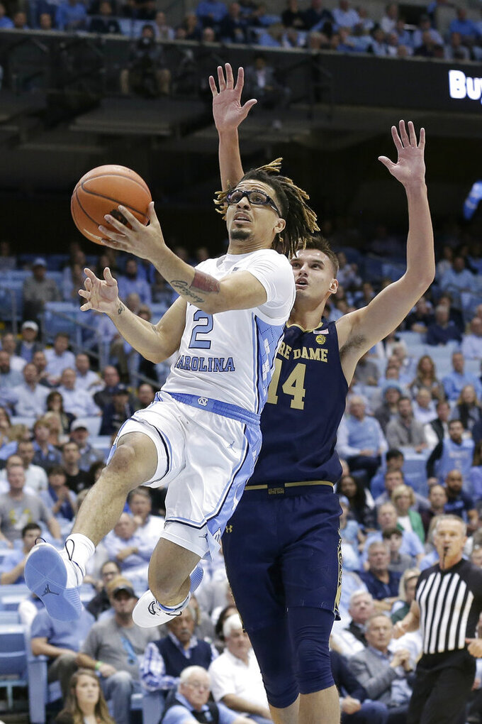 North Carolina guard Cole Anthony (2) drives to the basket while Notre Dame forward Nate Laszewski (14) defends during the first half of an NCAA college basketball game in Chapel Hill, N.C., Wednesday, Nov. 6, 2019. (AP Photo/Gerry Broome)