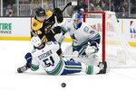 Boston Bruins' Jake DeBrusk (74) falls on Vancouver Canucks' Troy Stecher (51) as Jacob Markstrom (25) looks on during the second period of an NHL hockey game in Boston, Tuesday, Feb. 4, 2020. (AP Photo/Michael Dwyer)