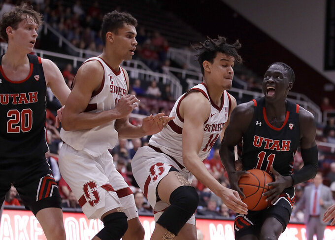 Utah's Both Gach, right, drives the ball against Stanford's Spencer Jones (14) in the second half of an NCAA college basketball game Wednesday, Feb. 26, 2020, in Stanford, Calif. (AP Photo/Ben Margot)