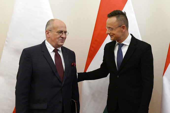 Hungarian Minister of Foreign Affairs and Trade Peter Szijjarto, right, welcomes his Polish counterpart, Zbigniew Rau in the Ministry of Foreign Affairs and Trade in Budapest, Hungary, Monday, Sept. 28, 2020. (Lajos Soos/MTI via AP)