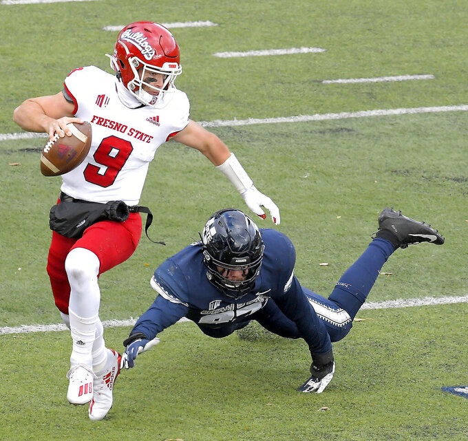 Fresno State quarterback Jake Haener (9) scrambles away from Utah State defensive lineman Jake Pitcher (97) during the first half of an NCAA college football game, Saturday, Nov. 14, 2020, in Logan, Utah. (Eli Lucero/Herald Journal via AP)