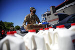 Rhode Island National Guard Pfc. Gerald Moniz distributes gallons of milk and produce along with volunteers with the Dairy Farmers of America to families in need, Wednesday, May 27, 2020, in Pawtucket, R.I. Dairy farmers have a milk surplus because demand has dropped as schools and restaurants closed during the coronavirus pandemic, and some farmers have had to pour excess milk away. Farmers donated the 4,300 gallons of milk given away today at McCoy Stadium. (AP Photo/David Goldman)