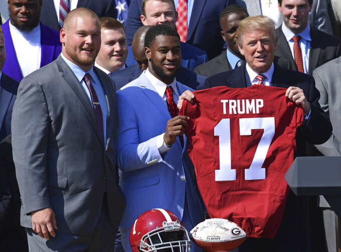 President Donald Trump, right, holds up a jersey he was presented with by Alabama team captains Bradley Bozeman, left, and Rashaan Evans, center, during an event for the 2017 NCAA National Champion University of Alabama football team on the South Lawn of the White House in Washington, Tuesday, April 10, 2018. (AP Photo/Susan Walsh)