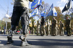 A handicapped Ukrainian army veteran watches a a rally marking Defender of Ukraine Day in centre Kyiv, Ukraine, Wednesday, Oct. 14, 2020. (AP Photo/Efrem Lukatsky)