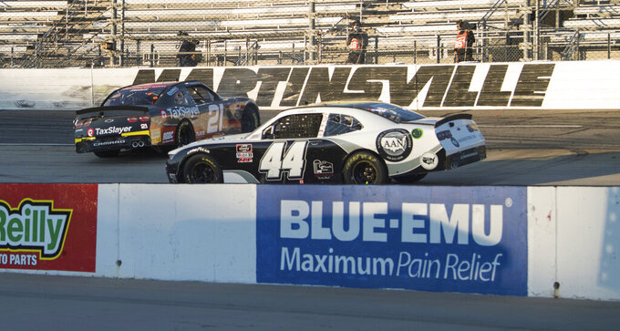 Myatt Snider (21) spins out in turn 3 as Tommy Joe Martins 944) drives by during a NASCAR Xfinity Series auto race at the Martinsville Speedway in Martinsville, Va., Saturday, Oct.31, 2020. (AP Photo/Lee Luther Jr.)