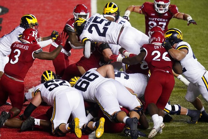 Michigan's Hassan Haskins (25) dives into the end zone for a touchdown during the third overtime of the team's NCAA college football game against Rutgers on Saturday, Nov. 21, 2020, in Piscataway, N.J. Michigan won 48-42. (AP Photo/Frank Franklin II)