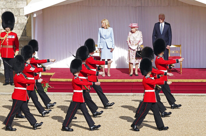 US President Joe Biden, background right and First Lady Jill Biden, centre left, stand  in the Quadrangle watching Grenadier Guards march by with Britain's Queen Elizabeth II, during a visit to Windsor Castle, in Windsor, England, Sunday June 13, 2021. The queen hosted President Joe Biden and First Lady Jill Biden at Windsor Castle, her royal residence near London. Biden flew to London after wrapping up his participation in a three-day summit of leaders of the world's wealthy democracies in Cornwall, in southwestern England. (Arthur Edwards/Pool via AP)