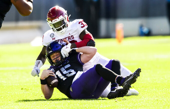 Oklahoma defensive end Marcus Stripling (33) sacks TCU quarterback Max Duggan (15) during the first half of an NCAA college football game, Saturday, Oct. 24, 2020, in Fort Worth, Texas. (AP Photo/Brandon Wade)