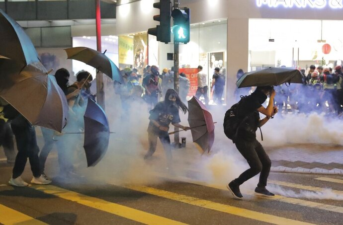 Protesters use umbrellas to protect themselves as they face police teargas in Hong Kong, Sunday, Nov. 10, 2019. Protesters smashed windows in a subway station and a shopping mall Sunday and police made arrests in areas across Hong Kong amid anger over a demonstrator's death and the arrest of pro-democracy lawmakers.Hong Kong is in the sixth month of protests that began in June over a proposed extradition law and have expanded to include demands for greater democracy and other grievances. (AP Photo/Kin Cheung)