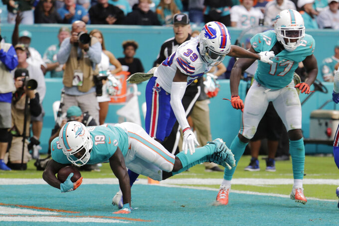 Miami Dolphins wide receiver Jakeem Grant (19) scores a touchdown during the second half at an NFL football game against the Buffalo Bills, Sunday, Nov. 17, 2019, in Miami Gardens, Fla. To the right are Buffalo Bills cornerback Levi Wallace (39) and Miami Dolphins wide receiver Allen Hurns (17). (AP Photo/Lynne Sladky)
