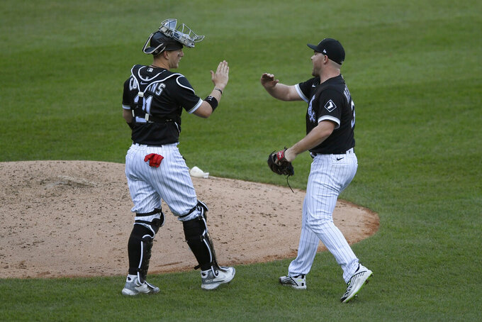 Chicago White Sox closing pitcher Liam Hendriks, right, celebrates with catcher Zack Collins, left, after defeating the Detroit Tigers in the first baseball game of a doubleheader Thursday, April 29, 2021, in Chicago. (AP Photo/Paul Beaty)