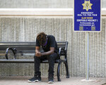 Cameron January sits alone after walking away from the press conference when the death of Pamela Turner — his mother —was being discussed in detail outside the Harris County Civil Courthouse on Thursday, April 8, 2021, in Houston. Attorney Benjamin Crump announced the filing of a federal lawsuit against Baytown Police officer Juan Delacruz in Turner's death, who was shot and killed on May 13, 2019. (Godofredo A. Vásquez/Houston Chronicle via AP)