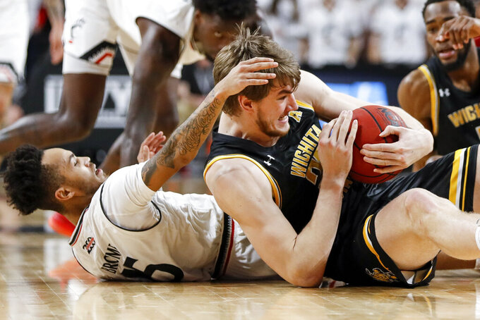 Wichita State's Asbjorn Midtgaard, right, and Cincinnati's Cane Broome, left, scramble for the ball in the first half of an NCAA college basketball game, Sunday, Feb. 17, 2019, in Cincinnati. (AP Photo/John Minchillo)