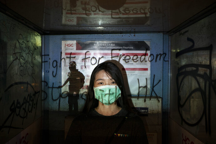 In this Oct. 19, 2019, photo, a 24-year-old protester who identified herself as Josephine, poses for a portrait as a projector displays a photograph, previously taken during the unrest, over her at a protest in Hong Kong. Josephine said she is afraid of the mask law,