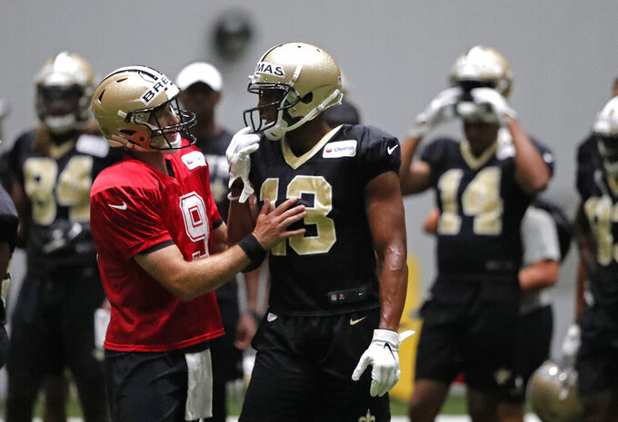 New Orleans Saints quarterback Drew Brees (9) talks with wide receiver Michael Thomas (13) during training camp at their NFL football training facility in Metairie, La., Thursday, Aug. 1, 2019. (AP Photo/Gerald Herbert)