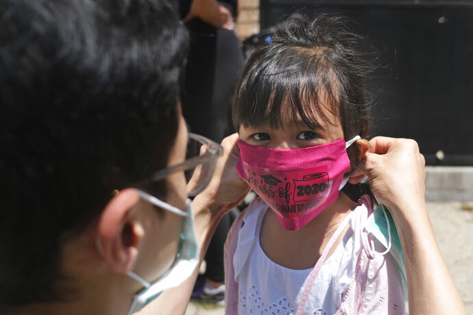 FILE - In this June 10, 2020, file photo, Olivia Chan's father helps her with new mask she received during a graduation ceremony for her Pre-K class in front of Bradford School in Jersey City, N.J. New Jersey Gov. Phil Murphy says the state's schools will be open for in-person instruction this fall, as long as COVID-19 trends don't worsen. The guidelines lay out a number of requirements, but also leave many decisions up to the state's roughly 600 school districts. (AP Photo/Seth Wenig, File)