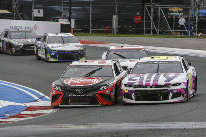 Christopher Bell, left, and Jimmy Johnson race side-by-side in a NASCAR Cup Series auto race at Charlotte Motor Speedway in Concord, N.C., Sunday, Oct. 11, 2020. (AP Photo/Nell Redmond)