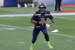 Seattle Seahawks quarterback Russell Wilson scrambles to pass against the San Francisco 49ers during the second half of an NFL football game, Sunday, Nov. 1, 2020, in Seattle. (AP Photo/Elaine Thompson)