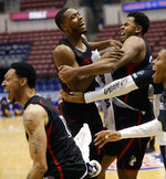 Northeastern's Shawn Occeus, center left, and Anthony Green, center right, hug as others celebrate defeating Hofstra 82-74 in an NCAA college basketball game at the Colonial Athletic Association men's basketball championship, Tuesday, March 12, 2019, in North Charleston, S.C. (AP Photo/Mic Smith)
