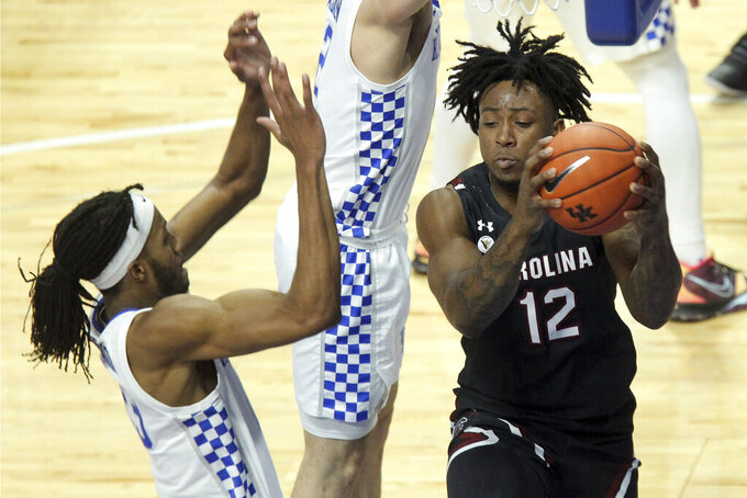South Carolina's Trae Hannibal (12) looks for help as Kentucky's Isaiah Jackson defends during the first half of an NCAA college basketball game in Lexington, Ky., Saturday, March 6, 2021. (AP Photo/James Crisp)