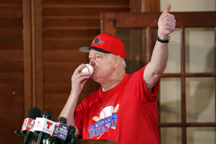 Pat Williams, co-founder of the NBA Orlando Magic basketball team, kisses a baseball at a news conference to announce a campaign to bring a Major League Baseball team to Orlando, Wednesday, Nov. 20, 2019 in Orlando, Fla. Williams brought good luck to the Orlando Magic by kissing ping pong balls before the NBA draft two years in a row bringing the number one picks twice. (AP Photo/John Raoux)