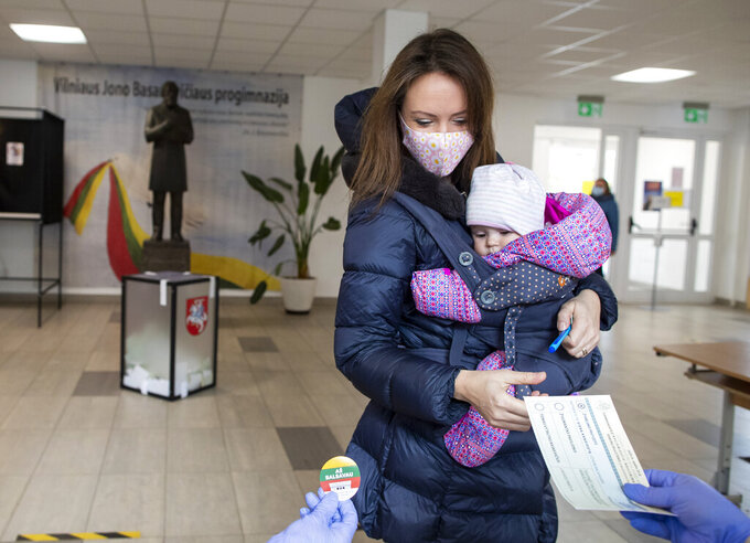 A woman with a child, wearing face mask to protect against coronavirus, arrives at a polling station during , arrives at a polling station during the second round of a parliamentary election in Vilnius, Lithuania, Sunday, Oct. 25, 2020. Polls opened Sunday for the run-off of national election in Lithuania, where the vote is expected to bring about a change of government following the first round, held on Oct. 11, which gave the three opposition, center-right parties a combined lead. (AP Photo/Mindaugas Kulbis)