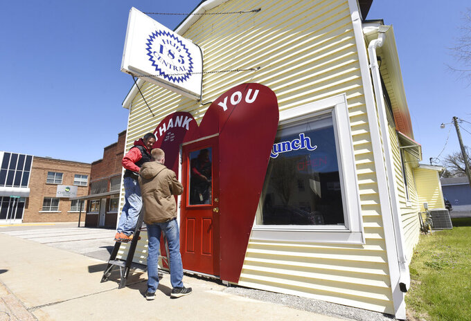 Tony Bertuca, owner of Hub 185 Central, and his son, Austin Bertuca, add names to a thank you heart sign framing the entrance to their restaurant Tuesday, April 21, 2020, in downtown Coloma, Mich. The restaurant is one of many who are only offering delivery and curbside pickup during the COVID-19 pandemic.(Don Campbell / The Herald-Palladium via AP)