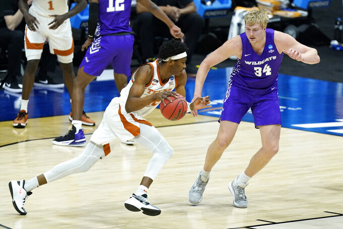 Texas' Kai Jones (22) drives against Abilene Christian's Kolton Kohl (34) during the first half of a college basketball game in the first round of the NCAA tournament at Lucas Oil Stadium in Indianapolis Saturday, March 20, 2021. (AP Photo/Mark Humphrey)