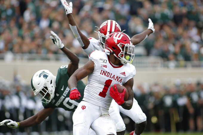 Indiana's Whop Philyor (1) returns a kick as Indiana's Taiwan Mullen, rear, illegally blocks Michigan State's Dominique Long (9) during the first quarter of an NCAA college football game, Saturday, Sept. 28, 2019, in East Lansing, Mich. (AP Photo/Al Goldis)