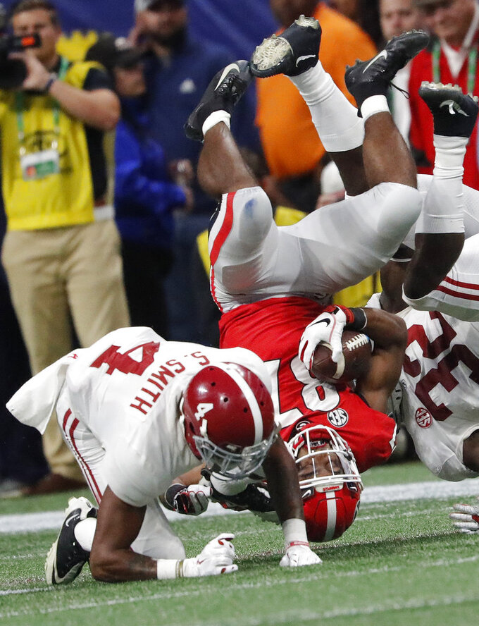 Alabama defensive back Saivion Smith (4) hits Georgia wide receiver Tyler Simmons (87) during the first half of the Southeastern Conference championship NCAA college football game, Saturday, Dec. 1, 2018, in Atlanta. (AP Photo/John Bazemore)
