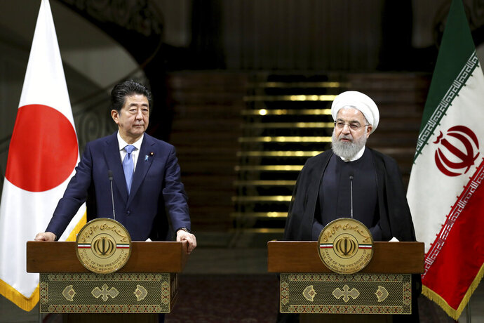 Iranian President Hassan Rouhani, right, speaks with media during a joint press conference with Japanese Prime Minister Shinzo Abe, after their meeting at the Saadabad Palace in Tehran, Iran, Wednesday, June 12, 2019. The Japanese leader is in Tehran on an mission to calm tensions between the U.S. and Iran. (AP Photo/Ebrahim Noroozi)