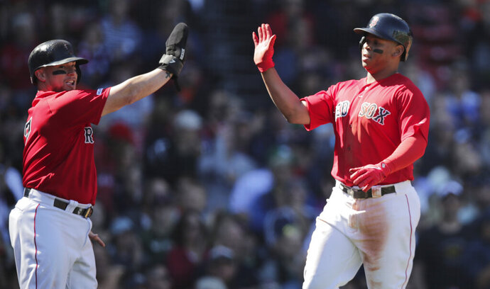 Boston Red Sox's Christian Vazquez, left, and Rafael Devers high-five after scoring on an Xander Bogaerts two RBI single during the second inning of a baseball game against the San Francisco Giants at Fenway Park in Boston, Thursday, Sept. 19, 2019. (AP Photo/Charles Krupa)