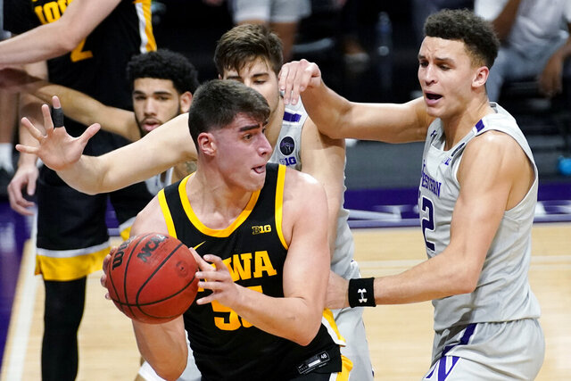 Iowa center Luka Garza (55) looks to pass against Northwestern forward Pete Nance, right, and center Ryan Young during the first half of an NCAA college basketball game in Evanston, Ill., Sunday, Jan. 17, 2021. (AP Photo/Nam Y. Huh)