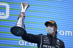 Mercedes driver Lewis Hamilton of Britain lifts his trophy on the podium after winning the Spanish Formula One Grand Prix at the Barcelona Catalunya racetrack in Montmelo, just outside Barcelona, Spain, Sunday, May 9, 2021. (AP Photo/Emilio Morenatti, Pool)