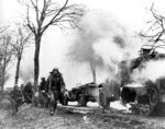 "FILE  - In this Dec. 1944 file photo, German infantrymen pass by burning captured American vehicles during the drive into Allied lines on the Western Front during the Battle of the Bulge. It was 75 years ago  that Hitler launched his last desperate attack to turn the tide for Germany in World War II. At first, German forces drove so deep through the front line in Belgium and Luxembourg that the month-long fighting came to be known as The Battle of the Bulge. When the Germans asked one American commander to surrender, the famous reply came: ""Nuts!"