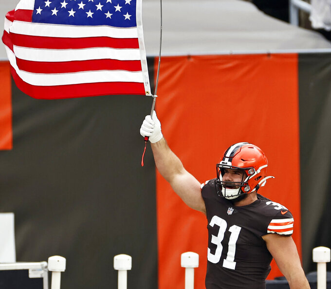FILE - In this Nov. 15, 2020, file photo, Cleveland Browns running back Andy Janovich holds up a United States flag before an NFL football game against the Houston Texans in Cleveland. Janovich was placed on the COVID-list on Monday, Nov. 16, 2020, a day after he played in a win over the Texans. (AP Photo/Ron Schwane, File)