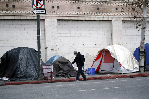 FILE - In this March 20, 2020, file photo, a man covers his face with a mask as he walks past tents on skid row in Los Angeles. The 9th U.S. Court of Appeals on Thursday, Sept. 23, 2021, overturned a federal judge's sweeping order that required the city and county of Los Angeles to quickly find shelter for all homeless people living on downtown's Skid Row. (AP Photo/Marcio Jose Sanchez, File)