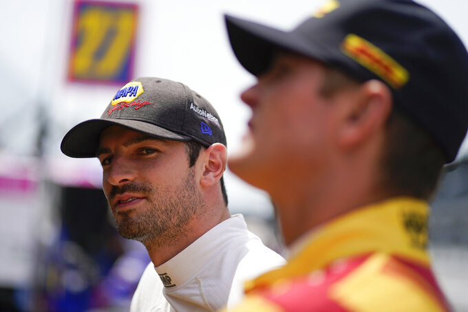Alexander Rossi, left, looks down pit lane during practice for the Indianapolis 500 auto race at Indianapolis Motor Speedway, Friday, May 21, 2021, in Indianapolis. (AP Photo/Darron Cummings)