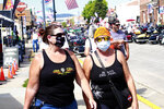 Thousands of bikers rode through the streets for the opening day of the 80th annual Sturgis Motorcycle rally Friday, Aug. 7, 2020, in Sturgis, S.D. Among the crowds of people in downtown Sturgis, a handful wore face masks to prevent the spread of COVID-19. (AP Photo/Stephen Groves)