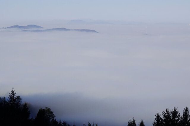 Hilltops and a TV tower are surrounded by fog in Sarajevo, Sunday, Dec. 8, 2019. The local government in Sarajevo issued a warning to residents to avoid spending time outdoors as extremely high pollution levels are being recorded in the air of Bosnian capital in last two days. (AP Photo/Eldar Emric)