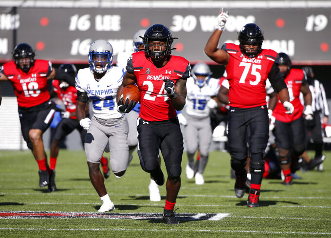 Cincinnati running back Jerome Ford (24) runs for a touchdown against Memphis as teammate John Williams (75) celebrates during the second half of an NCAA college football game Saturday, Oct. 31, 2020, in Cincinnati. Cincinnati won 49-10. (Photo by Gary Landers)