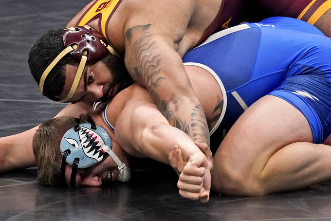 FILE - Minnesota's Gable Steveson, top, takes on Air Force's Wyatt Hendrickson during their 285-pound match in the second round of the NCAA wrestling championships in St. Louis, in this Thursday, March 18, 2021, file photo. Steveson looks to become one of the youngest U.S. wrestling gold medalists ever when he competes at 125 kilograms in Tokyo. (AP Photo/Jeff Roberson, File)