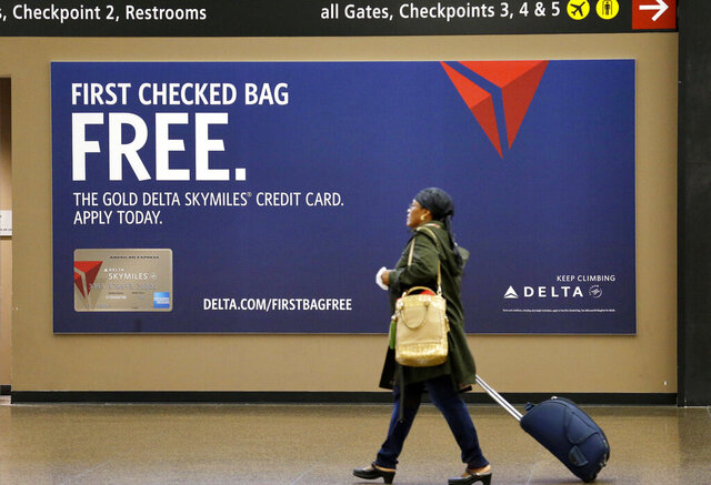 FILE - In this March 24, 2015, file photo, a traveler walks past a sign advertising a Delta Air Lines credit card at Seattle-Tacoma International Airport in SeaTac, Wash. A recent NerdWallet survey found that about a third of Americans plan to travel for 2020 spring break. In addition to earning points, using a travel credit card can provide valuable trip protections, as well as perks like free checked bags or lounge access. (AP Photo/Elaine Thompson, File)