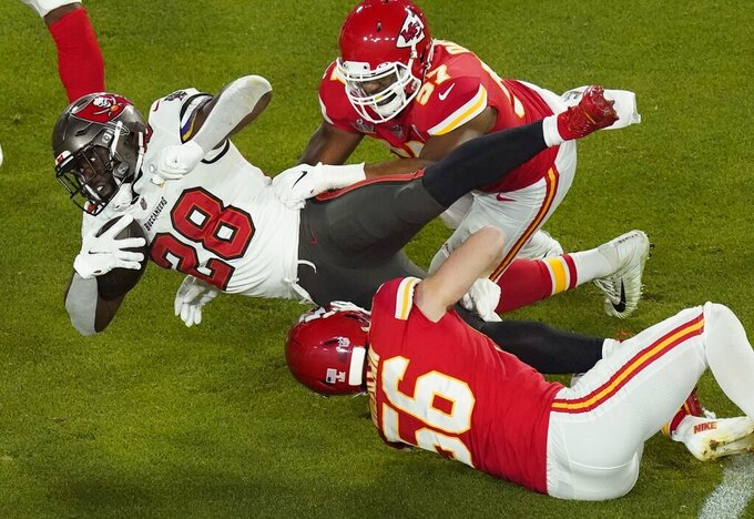 Tampa Bay Buccaneers' Leonard Fournette (28) is tackled by Kansas City Chiefs' Ben Niemann (56) and Alex Okafor (57) during the first half of the NFL Super Bowl 55 football game Sunday, Feb. 7, 2021, in Tampa, Fla. (AP Photo/Charlie Riedel)