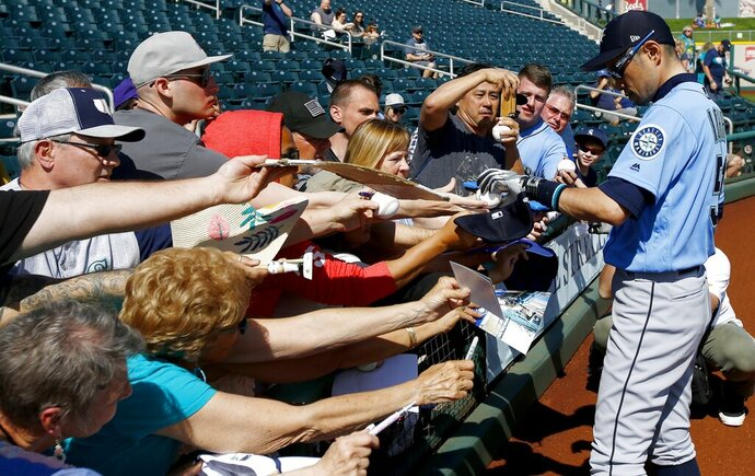 Seattle Mariners' Ichiro Suzuki, of Japan, signs autographs prior to a spring training baseball game against the Cleveland Indians Wednesday, Feb. 27, 2019, in Goodyear, Ariz. (AP Photo/Ross D. Franklin)