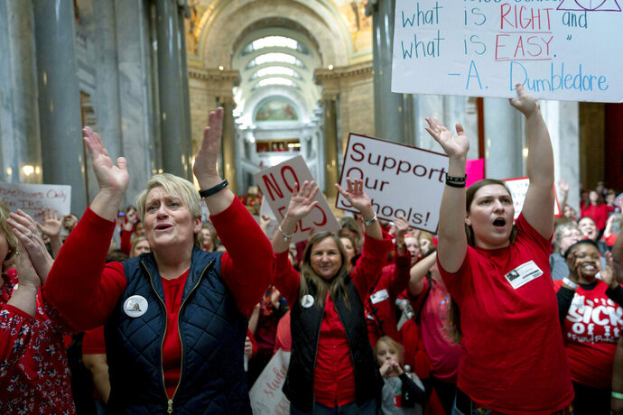 FILE - In this March 12, 2019 file photo, a group of the several hundred teachers gather to protest perceived attacks on public education at the Capitol in Frankfort, Ky. A Kentucky judge whose impartiality was questioned by Gov. Matt Bevin's legal team due to his social media interactions refused to step aside Wednesday, Sept. 4, 2019, from hearing a lawsuit brought by the governor's political nemesis over an investigation of teacher protests. (AP Photo/Bryan Woolston, File)