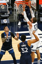 Memphis Grizzlies' Jonas Valanciunas (17) lays up a shot as Minnesota Timberwolves' Juancho Hernangomez (41) and Karl-Anthony Towns watch in the first half of an NBA basketball game, Wednesday, Jan. 13, 2021, in Minneapolis. (AP Photo/Jim Mone)