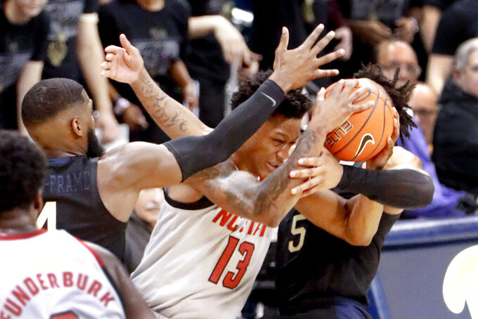 North Carolina State's C.J. Bryce (13) is fouled as Pittsburgh's Au'Diese Toney, right, and Jared Wilson-Frame, left, defend during the second half of an NCAA college basketball game, Saturday, Feb. 9, 2019, in Pittsburgh. North Carolina State won 79-76. (AP Photo/Keith Srakocic)
